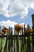 Clay broken pitchers hang wooden rural woven fence — Stock Photo