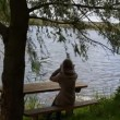 Stok video: Girl tree bench lake hair