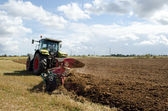Heavy agricultural machine tractor works in field — ストック写真
