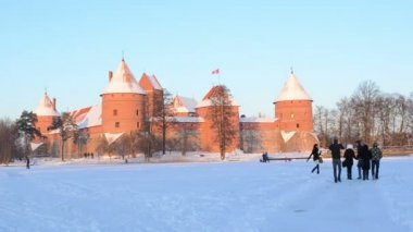 Beautiful evening sunset sunlight frozen snow covered castle and tourists active leisure on circa January 2013 in Trakai.