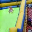 Kids climb and slide on inflatable rubber castle playground - Stock Photo