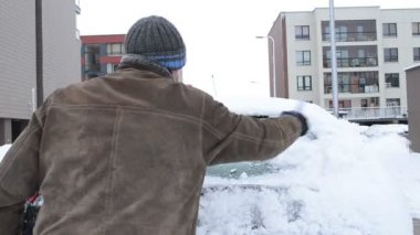 Man jacket knit hat cleaning snow car parking flat house winter — Vidéo