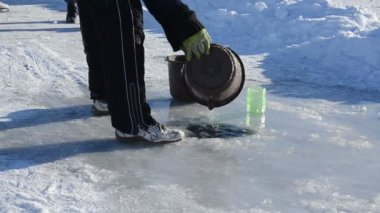 Man draw water frozen ice hole pour bucket winter skate site — Stockvideo