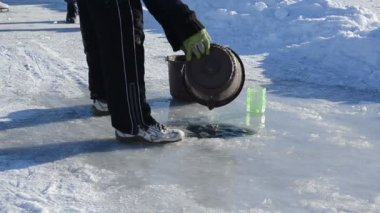 Man draw water frozen ice hole pour bucket winter skate site — Vidéo
