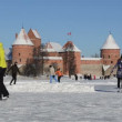 Stock Video: Active winter sport skate on ice frozen lake castle fort trakai
