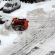 Small tractors clean snow street near flat houses parking lot — Stock Video