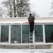 Stock Video: Worker mladder shovel tool clesnow greenhouse roof winter