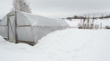 Homemade polythene greenhouse snow rotten apples winter garden — Stock Video