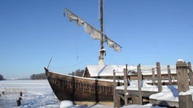 Retro wooden ship frozen lake ice pier sail move wind blue sky — Stockvideo
