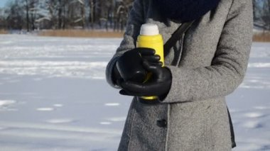 Woman coat gloves open yellow thermos pour tea coffee winter — Vidéo