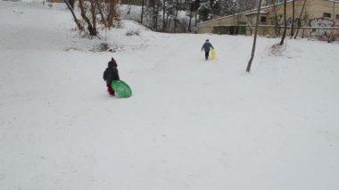 Schwester und bruder rauschen mit schnee-pad zu klettern, hill und folie — Stockvideo