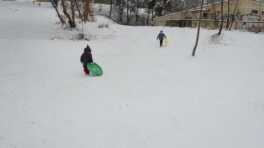 Sister and brother rushing with snow pad climb to hill and slide — Vídeo de stock