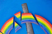 Colorful rainbow hand saw blue background concept — Stock Photo