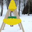 Closeup yellow swing toy move winter playground covered snow - Stock Photo