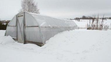Wooden diy homemade greenhouse polythene snow winter garden — Stock Video