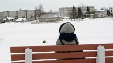 Woman bench houses frozen snow river shore smoke chimney winter — Stock Video