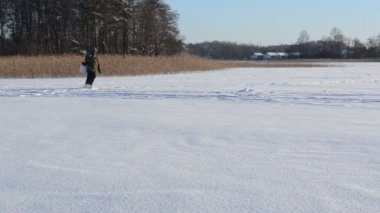 Fisherman drill box frozen lake ice fishing popular winter hobby — 图库视频影像