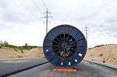 High voltage cable reel roll road construction — Stock Photo
