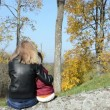 Stock Video: Wommother sit broken tree trunk daughter admire autumn tree