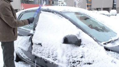 Man removing cleaning snow car window brush winter parking house — Stock Video