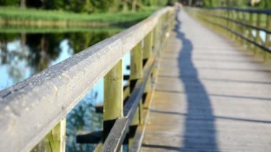 Wooden bridge railing closeup couple embrace clinch distance — Stockvideo