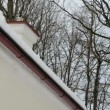 Stock Video: Closeup of slope roof corner and snow clefall down.