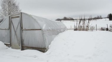 Homemade polythene greenhouse snow rotten apples winter garden — Stock Video