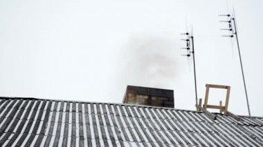 Old house slate roof snow dark smoke rise chimney antenna winter — Stock Video