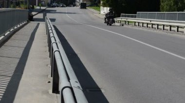Bikers ride motorcycles pass bridge road — Stock Video