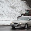Stock Video: Old tractor cleaning snow street pedestrian sidewalk winter car