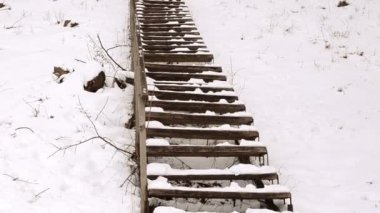 Wooden stairs railings huge steep hill cover snow winter park — Stock Video