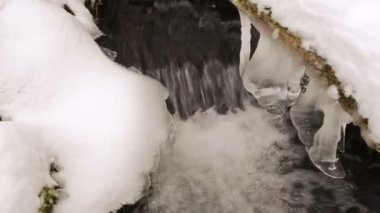 Closeup stream brook current flow snow icicles spring — 图库视频影像