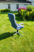 Blue office chair in sunny meadow — Stock Photo