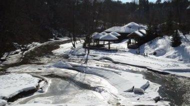 冻的河湾水木制房屋银行稻草屋顶盖雪 — 图库视频影像