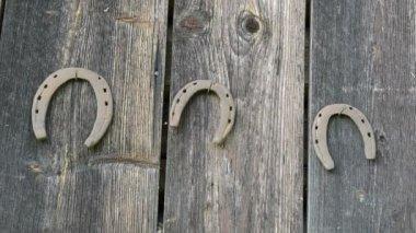 Ретро ржавые подковы двигаться висит старый деревянный дом стены — Стоковое видео