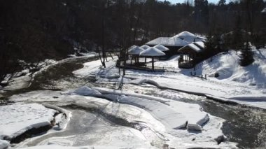Frozen river bay water wooden houses bank straw roof cover snow — Stock Video