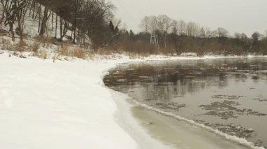 Auto gaan weg rivier waterkant dekking sneeuw drijft float stroom water — Stockvideo