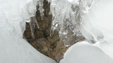 Closeup ice icicles flow melt water drop stones mountain cave — ストックビデオ