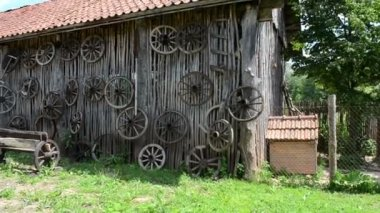 Retro carriage cart wheels hang on rural building wall bench — Stock Video