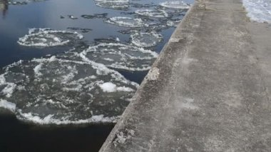 Pieces of frozen snow floats down the river along the edge — Stock Video