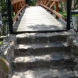 Stock Video: Walk imitation stone wooden bridge wildwater river park