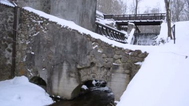 Vintage water mill building creek flow archs stones snow winter — Stock Video