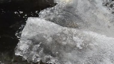 Ice covering rapid water flow stream air bubbles form winter — Stock Video