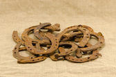 Stack old retro rusty horseshoes linen background — Stock Photo