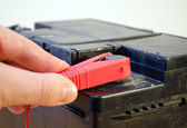Closeup hand plug car battery red clamp plus — Stock Photo
