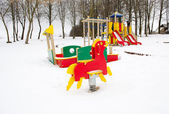 Empty colorful playground surrounded snow winter — Stock Photo