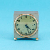 Grunge metallic retro clock stand blue background — Stock Photo