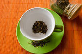 Afternoon green tea cup with on orange mat — Stock Photo