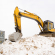 Excavator sand pit snow winter apartment house - Stock Photo