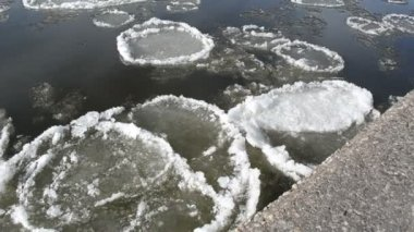 Dark river swims large pieces of frozen snow cement surfaces — Stock Video